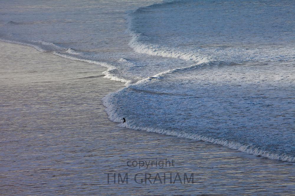 Lone surfer surfs waves crashing onto the beach at Woolacombe, North Devon, UK