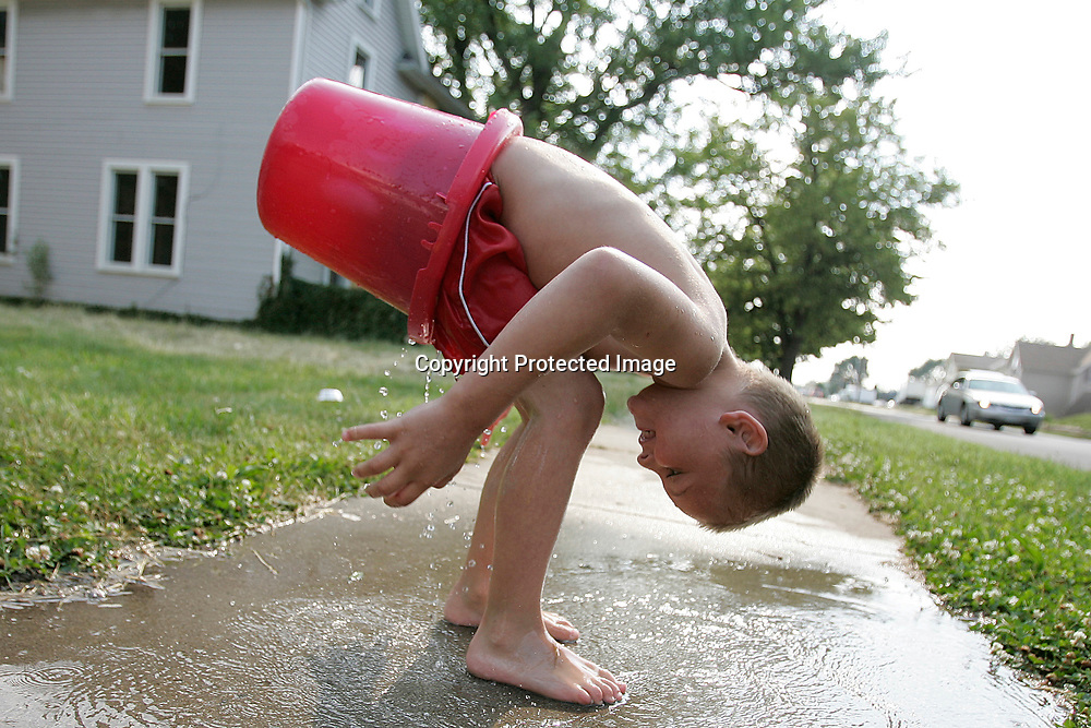 Isaah Younkin, 6, tries to remove a bucket from his bottom as he plays in his front yard Thursday on Indiana Avenue in South Bend.  He would fill the bucket up with water, sit on it and smile as it splashed.
