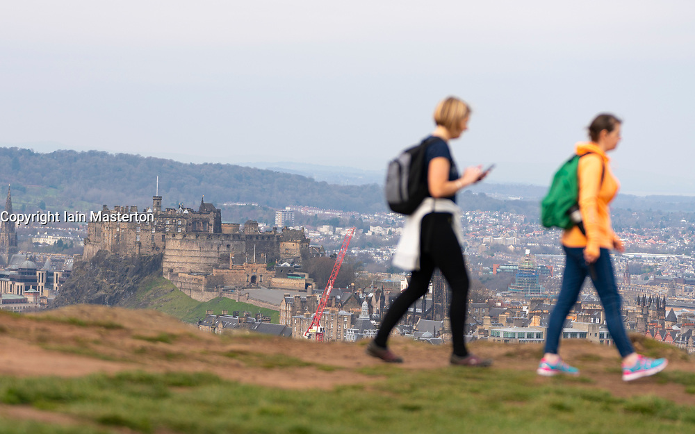 Edinburgh, Scotland, UK. 5 April, 2020. On the second Sunday of the coronavirus lockdown in the UK the public are outside taking their daily exercise. Women walking on Salisbury Crags in Holyrood Park with Edinburgh Castle in distance. Iain Masterton/Alamy Live News