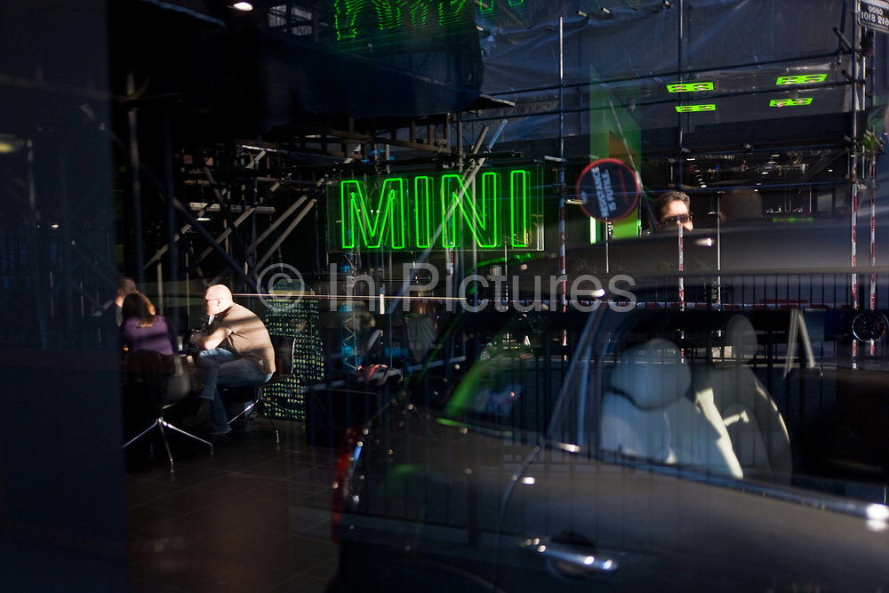 Interested potential buyers do business at a Mini car dealership in London's Park Lane. With sunlight streaming into the otherwise darkened design of the car showroom, a man and his partner sit at a table discussing their potential purchase with the prominent word Mini in green letters on the ceiling. The Mini is a small car that was made by the British Motor Corporation (BMC) and its successors from 1959 until 2000. The original is considered a British icon of the 1960s and its space-saving front-wheel-drive layout (which allowed 80% of the area of the car's floor pan to be used for passengers and luggage) influenced a generation of carmakers. In 1999 the Mini was voted the second most influential car of the 20th Century, behind the Ford Model T.