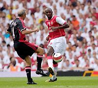 Photo: Daniel Hambury.<br />Arsenal v Ajax. Dennis Bergkamp Testimonial. 22/07/2006.<br />Arsenal's former star Patrick Vieira clips the ball past Dutch legand Johan Cruyff.
