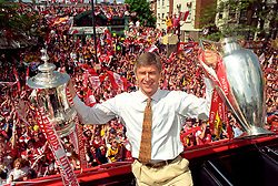 Arsenal boss Arsene Wenger poses with the FA  and League Cups as the team take a victory tour from the Highbury ground to Islington Town Hall today (Sunday) to celebrate their cup double.