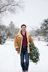 Hot cowboy in snow holding a Christmas Wreath