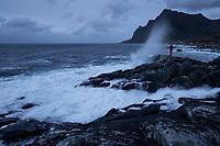 Female hiker stands on rugged coastline with crashing waves, Flakstadøy, Lofoten Islands, Norway