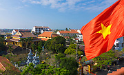 Rooftop view of Hoi An city with a Vietnamese flag blowing in the foreground