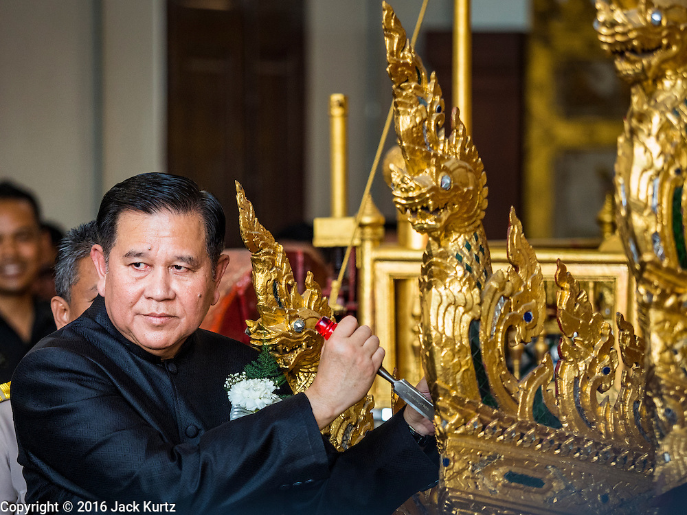 """19 DECEMBER 2016 - BANGKOK, THAILAND: A Thai government official prays during the """"Spirit Appeasing"""" Ceremony held for the Royal Chariots at the Bangkok National Museum. The chariots will be used to take the body of Bhumibol Adulyadej, the Late King of Thailand, and members of the Royal funeral cortege to the cremation site on Sanam Luang for His Majesty's cremation. This will be the first cremation of a Thai King since 1950, when King Bumibol's brother, Rama VIII, Ananda Mahidol, was cremated. The design of the royal crematorium is based on Buddhist cosmology, with the main peak of Mount Sumeru (also known as Meru in Hindu cosmology) at center and eight other peaks signifying the levels of the universe. The crematorium will be decorated with mythical creatures such as garuda, angels, and Himmapan Forest creatures. The structure and funeral pyre will stand just over 50 meters tall. The exact date of the King's cremation has not been set yet but is expected to be late next year.     PHOTO BY JACK KURTZ"""