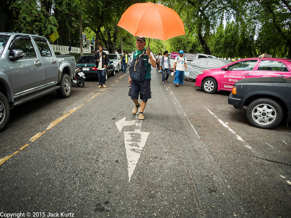 22 JULY 2015 - BANGKOK, THAILAND:  A man clears traffic for marchers near Government House in Bangkok. More than 100 people from Krabi province and members of the Save Andaman from Coal Network (SACN) have staged a series of marches and sit-ins outside the Prime Minister's office. They are opposed to plans to build an 800 megawatt coal fired power plant near southern Thailand's Andaman coast about 650 kilometers (400 miles) south of Bangkok. The area is famous for its pristine beaches. Residents worry that the coal fired power plant will pollute the area and send power to Bangkok.   PHOTO BY JACK KURTZ
