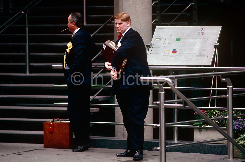 """Two businessmen in the insurance industry smoke a cigar and checks a watch outside the Lloyds of London address in the City of London, the capital's heart of the financial district. The post-modern architecture of the insurance underwriters Lloyd's building, home of the insurance institution Lloyd's of London which is located at number 1, Lime Street. Lloyd's is a British insurance market. It serves as a meeting place where multiple financial backers or """"members"""", whether individuals (traditionally known as """"Names"""") or corporations, come together to pool and spread risk. The Lloyds market began in Edward Lloyd's coffeehouse around 1688 and is today the world's leading insurance market providing specialist insurance services to businesses in over 200 countries and territories."""