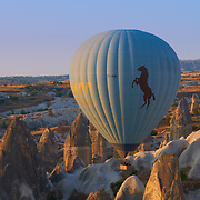 Hot air balloon flying between tuff rocks over Goreme valley in Cappadocia, Turkey