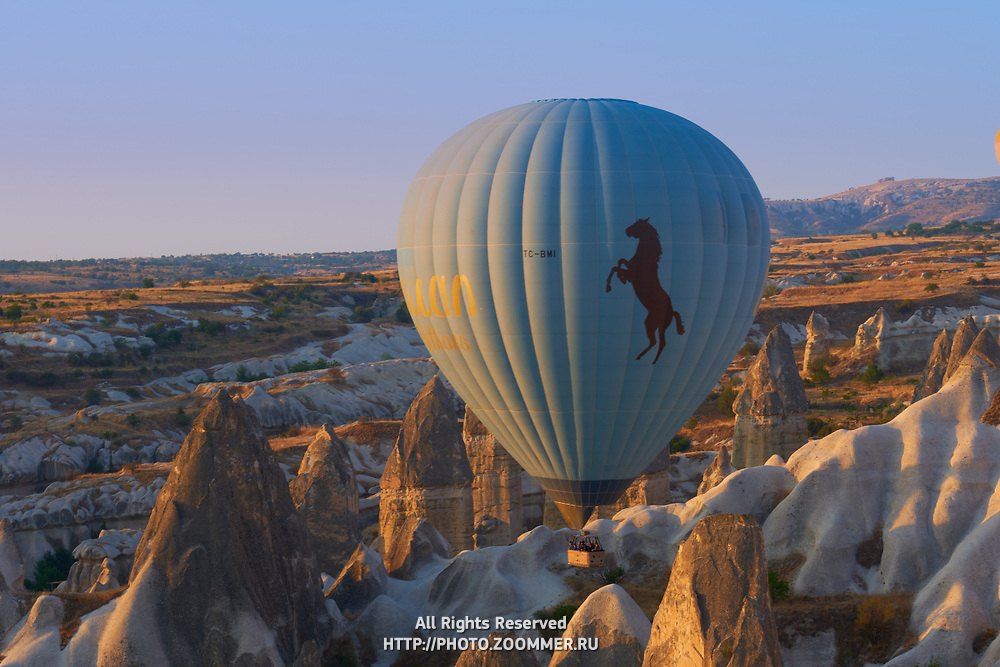 Hot air balloon flying between tuff rocks over Goreme valley in Cappadocia, Turkey