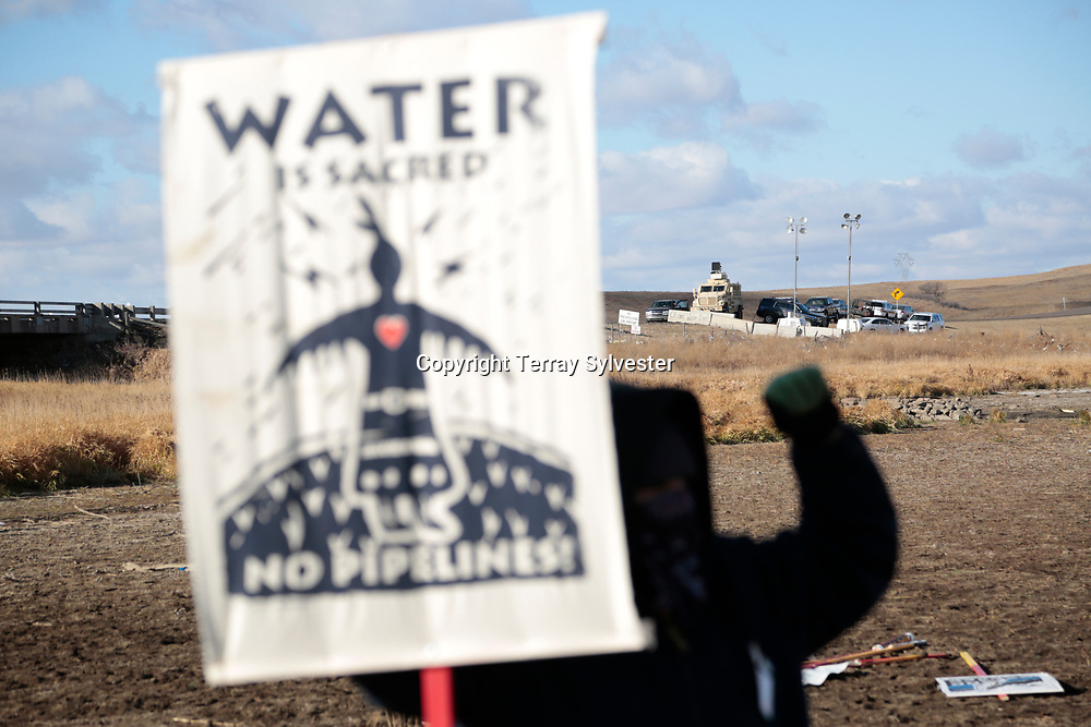 An opponent of the Dakota Access oil pipeline demonstrates near police vehicles on a tributary of the Missouri River on November 18, 2016. Cannon Ball, North Dakota, United States.