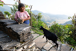 Woman with her cat in the small mountainside village of Ranjet while out on a ride on rented Royal Enfield Bullets (as mechanics were going through our Himalayans on the one rest day) in the hills around Pokhara during Motorcycle Sherpa's Ride to the Heavens motorcycle adventure in the Himalayas of Nepal. After 6 days on the road, the riders and the bikes both had a rest day in Pokhara. Sunday, November 10, 2019. Photography ©2019 Michael Lichter.