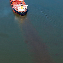 Aerial Photograph of the petroleum vessel  Along delaware river near  philadelphia, pa. Notice oil excess or disbursing from under ship.