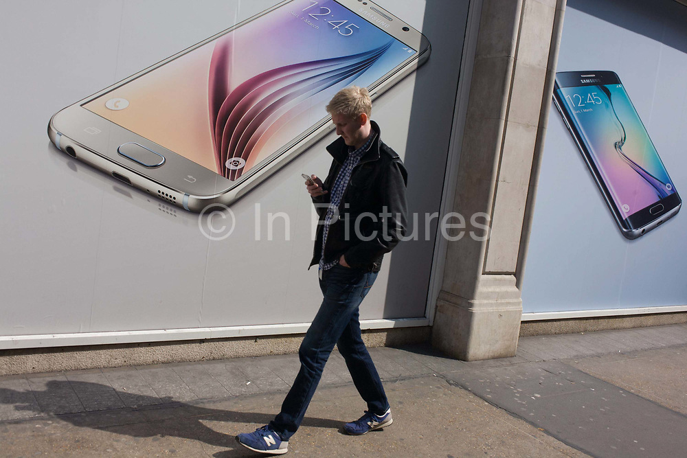 Phone user walks past Samsung shop window ad for new S6 model. Walking along the street in London's Soho, we see the man walking with his own handset checking messages or listening to music. In the background is Samsung's latest smartphone model, being launched in all media this week in an attempt to win back users from a new iPhone range. Samsung Galaxy S6 and Samsung Galaxy S6 Edge are Android smartphones manufactured and marketed by Samsung Electronics. The S6 and S6 Edge jointly serve as successors to the Galaxy S5. The smartphones were officially unveiled in a press conference at Mobile World Congress on 1 March 2015.