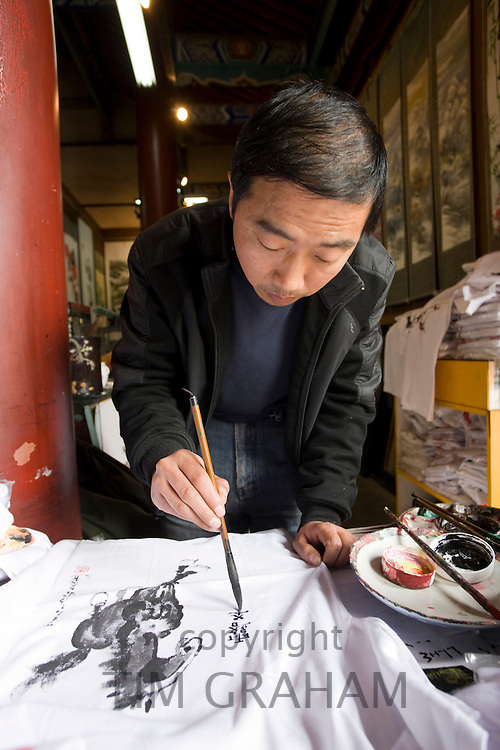 Traditional Chinese artist at work on souvenirs at Small Wild Goose Pagoda gift shop, Xian, China