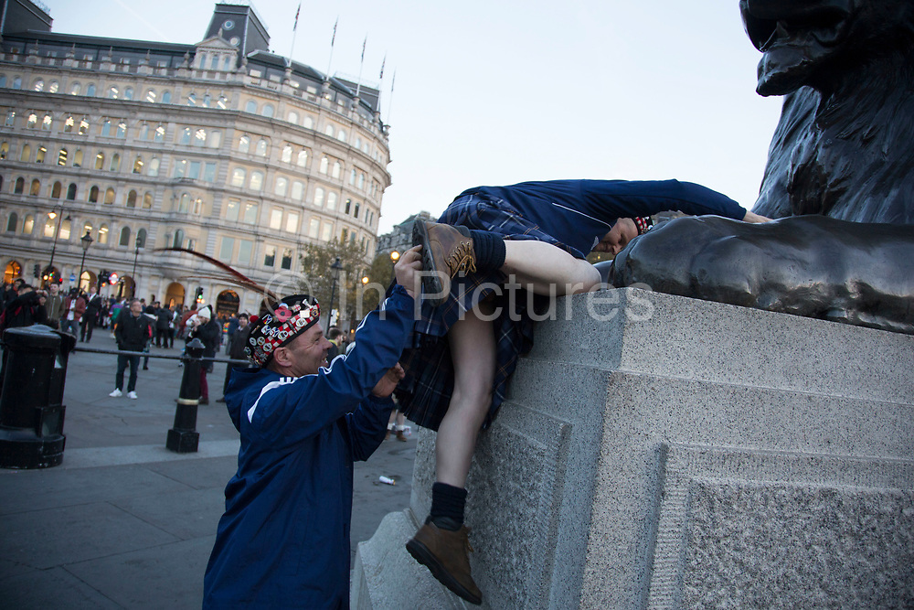 Scotland fans in joyous mood drinking and singing together in Trafalgar Square ahead of their football match, England vs Scotland, World Cup Qualifiers Group stage on 11th November 2016 in London, United Kingdom. The Home International rivalry between their respective national teams is the oldest international fixture in the world, first played in 1872.