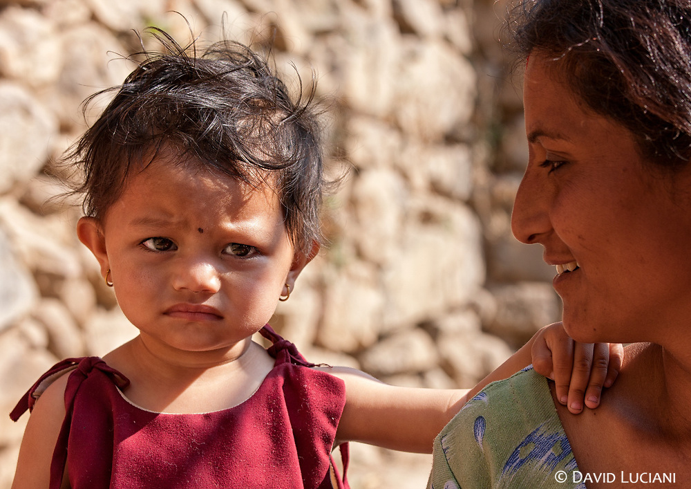 A suspicious little girl in Kirtipur, putting her hand on her mother's shoulder while i'm trying to get a smile from her.