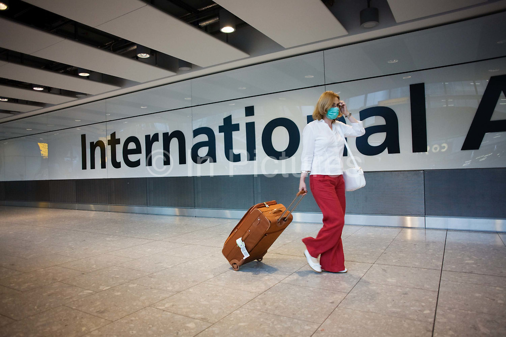 """Towing her suitcase after havng cleared International Customs, a masked female passenger walks through arrivals in Terminal 5 of Heathrow Airport. In the belief that she is protecting herself from airborne diseases and infections, the lady walks smartly through the concourse not wishing to be exposed to Swine Flu or perhaps SARS, in a hectic public place where such bacteria can be transmitted from one human being to another. From writer Alain de Botton's book project """"A Week at the Airport: A Heathrow Diary"""" (2009)."""