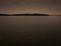 A single fishing boat looks lonely a distance from shore in the Hood Canal fjord in Puget Sound, western Washington state, USA.
