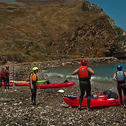 Paddlers setting out to explaore the volcanic sea caves that honeycomb the shoreline of Santa Cruz Island, Channel Islands National Park, CA.