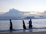 Locals walk through surf at Papanasham Beach (Beach of Redemption), Varkala, Kerala, India
