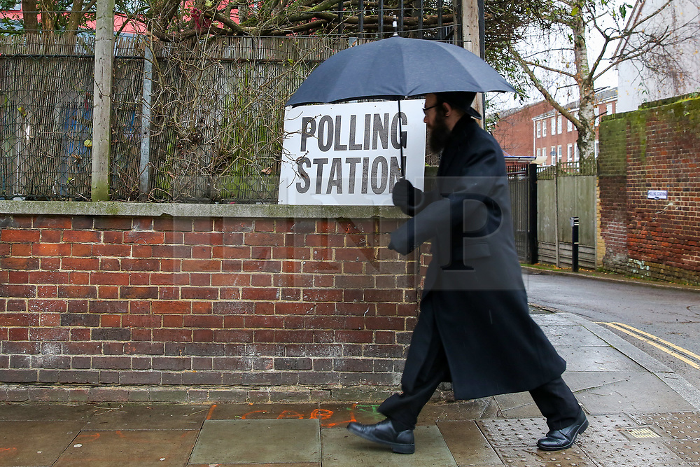 © Licensed to London News Pictures. 12/12/2019. London, UK. An Orthodox Jewish man shelters from the rain as he walks past a polling station sign in Stamford Hill, north London. Voters are voting today, as the nation decides the next UK Government in the first December General Election since 1923.  Photo credit: Dinendra Haria/LNP