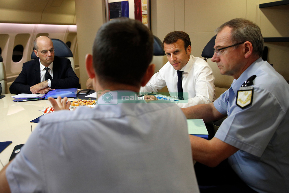 France's President Emmanuel Macron, 2nd right, confers with officials aboard the presidential plane en route to Guadeloupe Island, the first step of his visit to French Caribbean islands, Tuesday, Sept. 12, 2017. Seated at the table from left are French Education Minister Jean-Michel Blanquer, director of the rescue service (Securite Civile), Jacques Witkowski, back to camera, and Director General of the Gendarmerie Nationale, Richard Lizurey. Photo by Christophe Ena/Pool/ABACAPRESS.COM