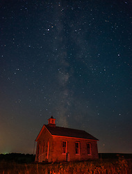 The evening sky reveals stars over the Lower Fox Creek Schoolhouse located in the Tallgrass Prairie National Preserve in the Kansas Flint Hills. The school, on the National Historic Register of Historic Places, was built on land donated by cattleman Stephen F. Jones. Built in 1882, the one-room school had its first classes in 1884. Typical enrollment was between one to 19 students of all grades. The school was closed in 1930 and restored in 1968 by the Garden Clubs in the Mid-East District of Kansas. The 10,894-acre Tallgrass Prairie National Preserve is located in Chase County near the towns of Strong City and Cottonwood Falls. Less than four percent of the original 140 million acres of tallgrass prairie remains in North America. Most of the remaining tallgrass prairie is in the Flint Hills in Kansas. Tallgrass Prairie National Preserve is the only unit of the National Park Service dedicated to the preservation of the tallgrass prairie ecosystem. The Tallgrass Prairie National Preserve is co-managed with The Nature Conservancy. (PHOTOGRAPHER'S NOTE: Red light is from red filter on photographer's headlamp.)