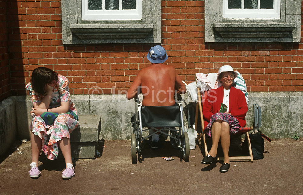 Ageing, elderly parents sunbathe with a teenage daughter as the father oddly faces a brick wall while sat in his wheelchair. Looking bored with the family holiday, the young lady of about 18 years of age, sits on a concrete block, the highlight of a vacation at home in Britain, rather than a package trip in mainland Europe. The father has a tanned back but sits facing the brick wall in an eccentric, odd way of sunbathing. He is obviously disabled and can't reach a beach via steps and perhaps this is why they have opted for this rather desolate corner of the seaside town resort.