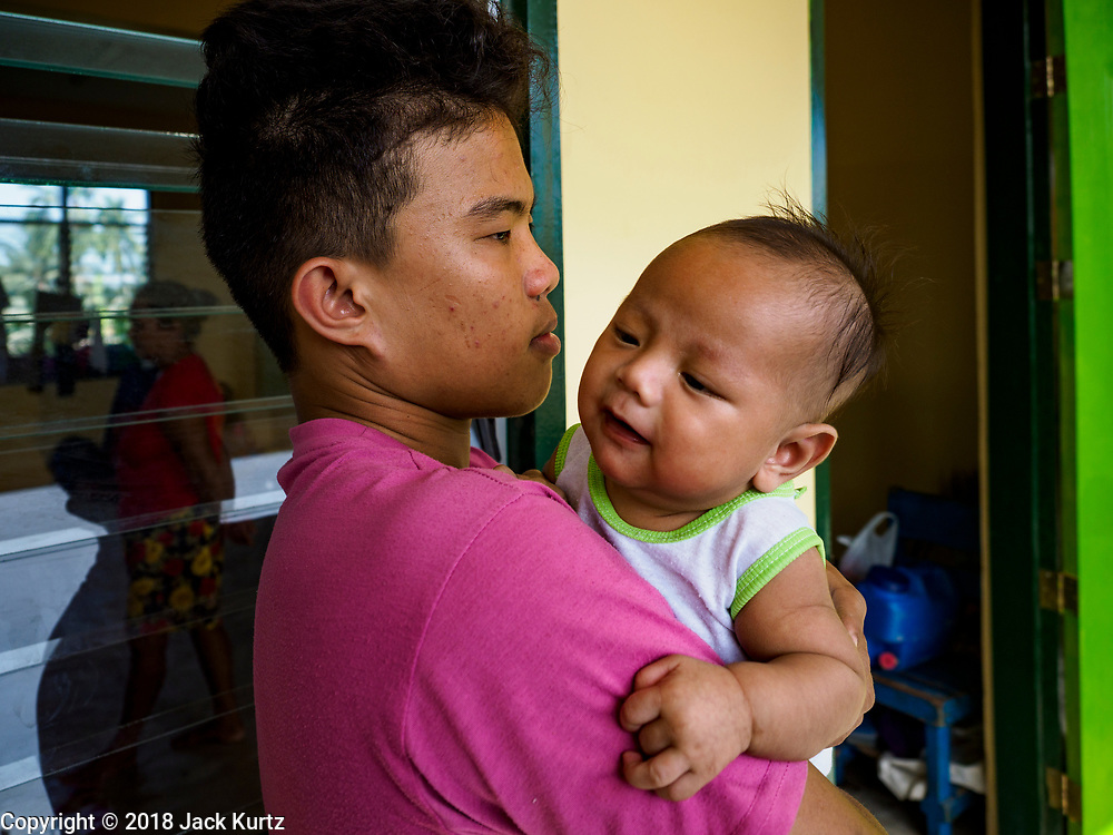 24 JANUARY 2018 - LIGAO, ALBAY, PHILIPPINES: JOSEPH CARULLO, 17, tries to comfort his nephew, ZUES TIMOTHY CASIM, 2 months old. They are temporarily living in in Ligao with 1,849 other people from the volcano. The Mayon volcano continued to erupt Tuesday night and Wednesday forcing the Albay provincial government to order more evacuations. By Wednesday evening (Philippine time) more than 60,000 people had been evacuated from communities around the volcano to shelters outside of the 8 kilometer danger zone. Additionally, ash falls continued to disrupt life beyond the danger zones. Several airports in the region, including the airport in Legazpi, the busiest airport in the region, are closed indefinitely because of the amount of ash the volcano has thrown into the air.    PHOTO BY JACK KURTZ