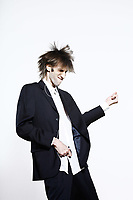 studio shot portrait of a young funny expressive thin and tall man on isolated background listenning music to a mp3 player beeing an Air guitar hero faking to play