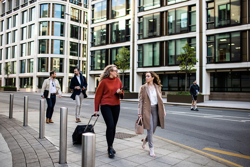 Business people walking through St Helier town and past corporate office buildings in the banking and finance centre of Jersey, CI