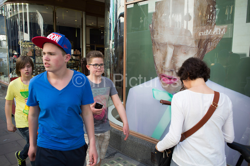 Photograph of a man's head wrapped like a parcel makes an interesting street scene as people interact. New Bond Street, London, UK. A weird visual juxtaposition is created as people integrate with the large scale printed picture.