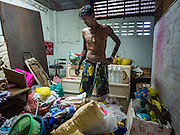 28 SEPTEMBER 2015 - BANGKOK, THAILAND:  A man packs on the day he moved out of his home at Wat Kalayanamit. Fifty-four homes around Wat Kalayanamit, a historic Buddhist temple on the Chao Phraya River in the Thonburi section of Bangkok, are being razed and the residents evicted to make way for new development at the temple. The abbot of the temple said he was evicting the residents, who have lived on the temple grounds for generations, because their homes are unsafe and because he wants to improve the temple grounds. The evictions are a part of a Bangkok trend, especially along the Chao Phraya River and BTS light rail lines. Low income people are being evicted from their long time homes to make way for urban renewal.   PHOTO BY JACK KURTZ