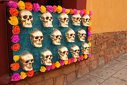 North America, Mexico, Oaxaca Province, Oaxaca, display of bronze skulls and tissue paper flowers, Day of the Dead (Dias de los Muertos) celebration