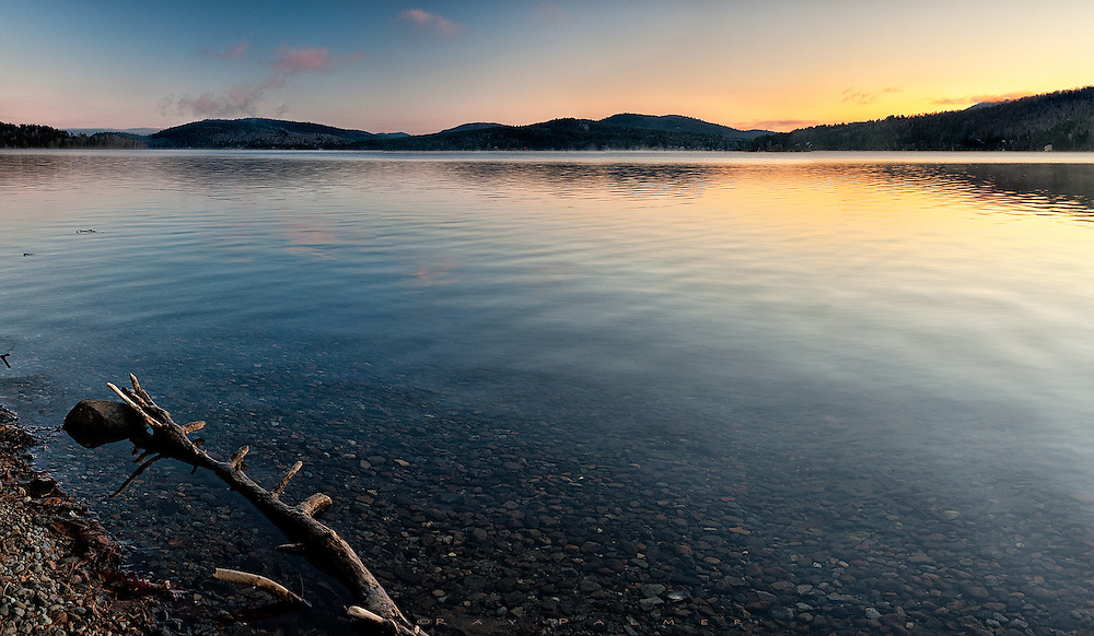 Adirondacks, NY<br /> There was a chill by the water, and slow fingers struggled with camera and tripod while waiting out the sunrise on Schroon Lake.  But the cold was soon forgotten as the sparse clouds picked up color and the light intensified.  In another few weeks this lake will be a solid ice sheet, dotted with fishing shanties, snowmobiles, and even pickup trucks.  For now, it is giving up the last of it's heat each day, contrails lifting off the water into the colder air above.