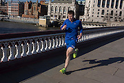 Male lunchtime jogger runs over Blackfriars Bridge.