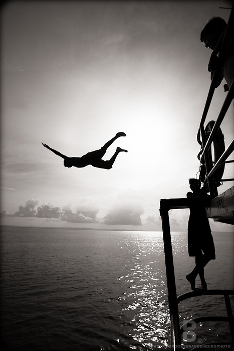Local young men and boys jump and dive off of the top of a ferry boat that must have been about 35-40 feet high, as there silhouettes soar through the air.