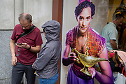 A man checks directions next to the image of a genie and his lamp in Long Acre, on 13th August 2018, in London, England.