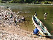 """Afternoon at the Nam Ou riverside in the remote and roadless Laoseng minority village of Ban Phouxom, Phongsaly Province, Lao PDR. The Nam Ou river (a tributary of the Mekong) connects small riverside villages and provides the rural population with food for fishing. It is a place where children play and families bathe, where men fish and women wash their clothes. But this river and others like it, that are the lifeline of rural communities and local economies are being blocked, diverted and decimated by dams. The Lao government hopes to transform the country into """"the battery of Southeast Asia"""" by exporting the power to Thailand and Vietnam."""