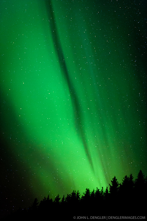 A spectacular display of the Aurora Borealis or as it is commonly called, the northern lights, occurred the evening of November 8 through the early morning of November 9, 2013 over Haines, Alaska. The luminous glow in the upper atmosphere stretched across the skies above the Lynn Canal from Skagway to Juneau. The bottom edge of an aurora is typically 60 miles high with the top edge at an altitude of 120 to 200 miles, though sometimes high altitude aurora can be as high as 350 miles. The collision of sun storm electrons and protons with different types of gas particles in Earth's atmosphere cause the different colors. Green, the most common color, is caused by the collision of electrons with atoms of with atomic oxygen.