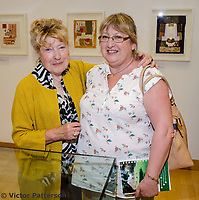 """Mavis Thomson, artist, right, with married sister, Barbara Wilson. Mavis, who lives in Enniskillen, Co Fermanagh, N Ireland, is a member of the Royal Ulster Academy, Ulster Society of Woman Artists, Watercolour Society of Ireland, Ulster Watercolour Society and the Turner Society. Taken at art exhibition, """"Three Ways of Seeing"""", in the Strule Arts Centre, Omagh, Co Tyrone, 25th May 2018. The event showcased the work of not just Mavis, but her equally talented daughters, Marion and Sydney. 201805254880<br /> <br /> Copyright Image from Victor Patterson, 54 Dorchester Park, <br /> Belfast, UK, BT9 6RJ<br /> <br /> t1: +44 28 9066 1296 (from Rep of Ireland 048 9066 1296)<br /> t2: +44 28 9002 2446 (from Rep of Ireland 048 9002 2446)<br /> m: +44 7802 353836<br /> <br /> victorpatterson@me.com<br /> victorpattersonbelfast@gmail.com<br /> <br /> Please see my Terms and Conditions of Use at victorpatterson.com. It is IMPORTANT that you familiarise yourself with them.<br /> <br /> Images used on the Internet incur an additional cost and must be visibly watermarked i.e. ©Victor Patterson within the body of the image and copyright metadata must not be deleted. Images used on the Internet have a size restriction of 4kbs and are chargeable at rates available at victorpatterson.com.<br /> <br /> This image is available only for the use of the download recipient i.e. television station, newspaper, magazine, book publisher, etc, and must not be passed on to any third party. It is also downloaded on condition that each and every usage is notified within 7 days to victorpatterson@me.com<br /> <br /> The right of Victor Patterson (or the named photographer) to be identified as the author is asserted in accordance with The Copyright Designs And Patents Act (1988). All moral rights are asserted."""