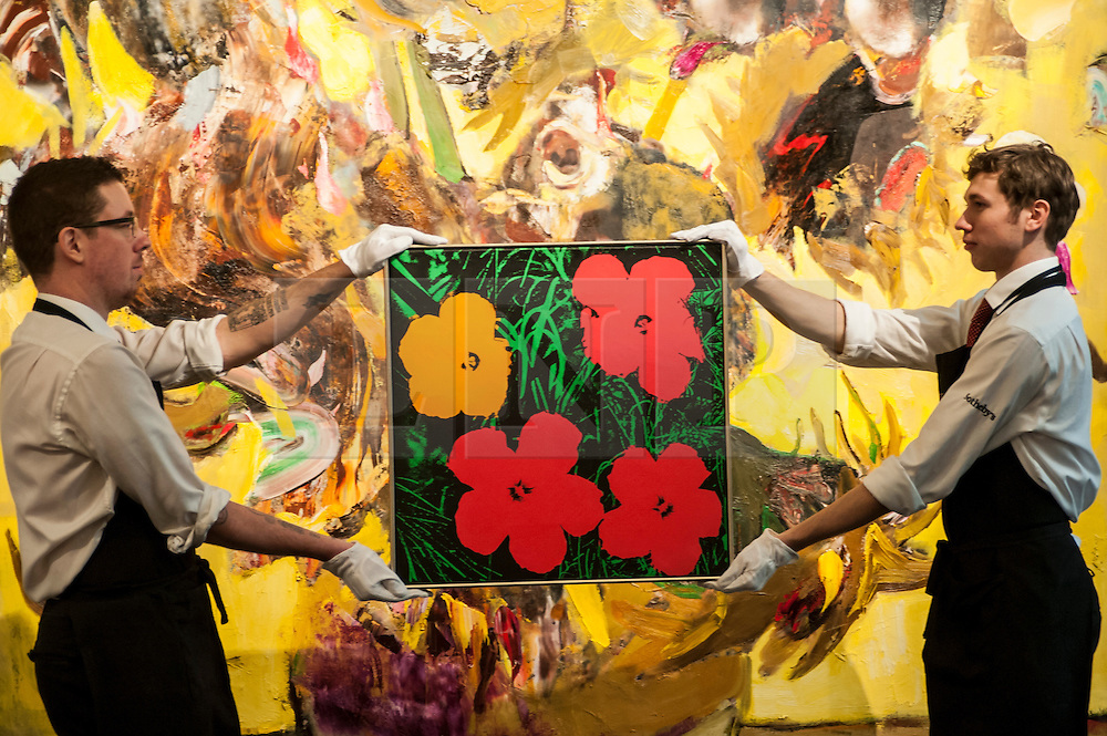 """© Licensed to London News Pictures. 28/01/2016. London, UK.   """"Flowers"""" by Andy Warhol (est. £1.3-1.8m) is shown in front of """"The Sunflowers"""" by Adrien Ghenie (est. £0.4-0.6m), at Sotheby's preview of its upcoming Impressionist, Modern & Surrealist art sale on 3 February featuring works by some of the most important artists of the 20th century.  The combined total of the evening sale is expected to exceed £100m. Photo credit : Stephen Chung/LNP"""