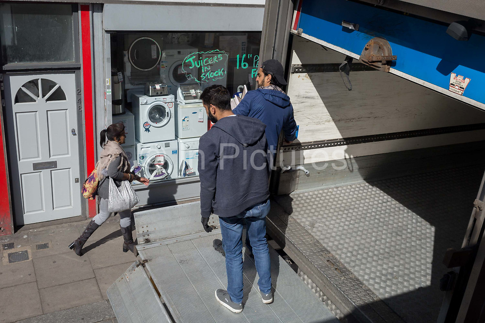 Two men on the tailgate of a delivery lorry look down at a passing woman on the Walworth Road in Southwark, south London, on 13th May, in London, England.