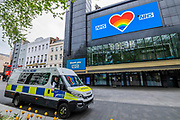 Police vehicles pass by as the Odeon Leicester Square show love for the NHS with a huge  rainbow heart on its screen - The 'lockdown' continues for the Coronavirus (Covid 19) outbreak in London.