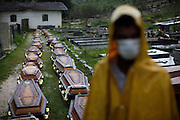Wearing face masks to prevent infections, a man stand next to coffins containing bodies of landslides victim at a cemetery in Nova Friburgo, Brazil, Saturday, Jan. 15, 2011. <br /> <br /> A series of flash floods and mudslides struck several cities in Rio de Janeiro State, destroying houses, roads and more. More than 900 people are reported to have been killed and over 300 remain missing in this, Brazil's worst-ever natural disaster.