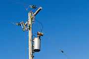 Electricity transformer, power lines and insulators on a wooden power pole. <br /> <br /> Editions:- Open Edition Print / Stock Image