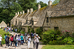 Many Asian tourists visiting Arlington Row historic former weavers cottages in Bibury ,Gloucestershire, Cotswolds ,England