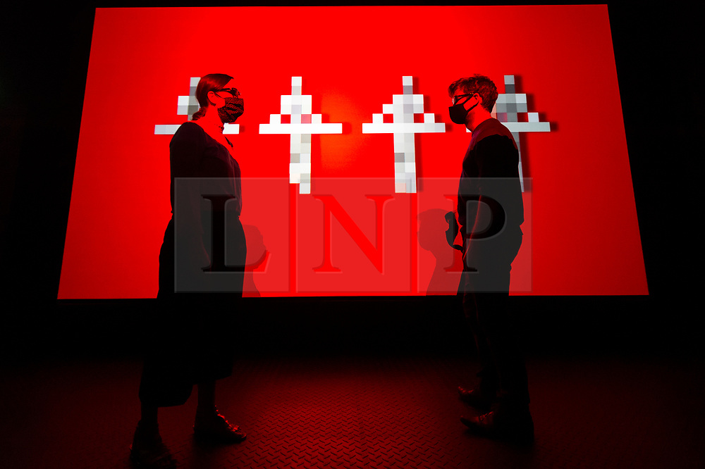 """© Licensed to London News Pictures. 28/07/2020. CITY, UK.  Staff members pose in front of the 3D video installation """"12345678"""", 2017, by Kraftwerk.  Preview of """"Electronic: From Kraftwerk to The Chemical Brothers"""" at the Design Museum in Kensington which is reopening after coronavirus lockdown.  The new exhibition explores the hypnotic world of electronic music, from its origins to its futuristic dreams.  The show runs 31 July 2020 – 14 February 2021 with visitors required to adhere to strict social distancing guidelines.  Photo credit: Stephen Chung/LNP"""