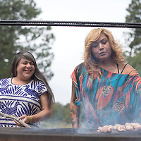 Alama Rosa Silva-Banuelos, left, and Sasha Fox help prepare lunch on the grill for the Northwest New Mexico Pride gathering in Vanderwagon September 27.